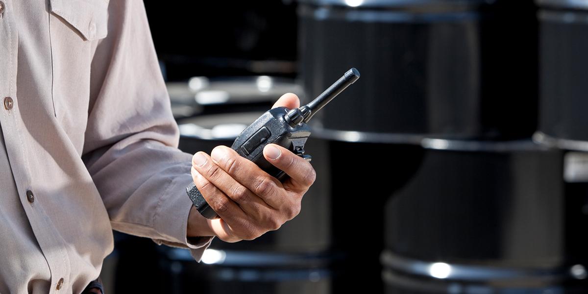 African American man holding walkie-talkie, by storage barrels